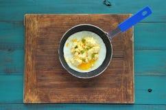 La disposizione piana delle uova rimescolate è servito in una penna rustica Fotografie Stock