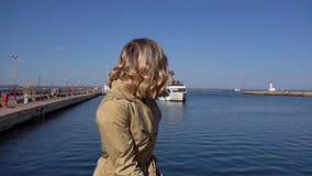 La distancia de la mujer rubia joven atractiva en foso con la maleta del vintage se está sentando en el embarcadero de Jacht metrajes