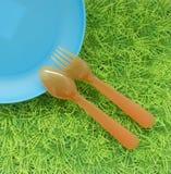 La diversión coloreó el fondo con las cucharas, bifurcaciones, plato en hierba verde Imagen de archivo