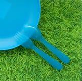 La diversión coloreó el fondo con las cucharas, bifurcaciones, plato en hierba verde Imágenes de archivo libres de regalías