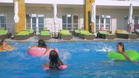 La diversión del verano en piscina, las novias alegres en bañadores con el pelo largo se divierte en la piscina azul que salpica  almacen de video