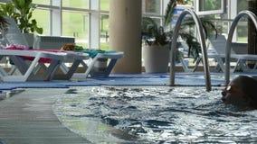 La diversión divertida de la niña emerge del agua de la turquesa en la piscina Cámara lenta almacen de video
