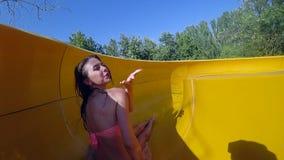 La diversión en parque del agua, pares jovenes de amantes que van abajo del tobogán acuático grande y muchacha da beso del aire e metrajes