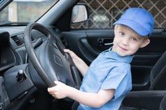 La diversión, feliz, muchacho está detrás de la rueda del coche y de mirarnos Fotos de archivo