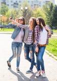 La diversión hawing de los adolescentes felices pasa el tiempo junto en el parque de la ciudad Foto de archivo