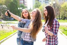 La diversión hawing de los adolescentes felices pasa el tiempo junto en el parque de la ciudad Foto de archivo libre de regalías