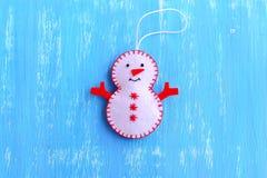 La diversión sentía el ornamento del muñeco de nieve de la Navidad aislado en un fondo de madera azul Cómo hacer un ornamento del Foto de archivo libre de regalías