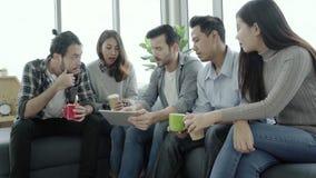La diversité créative multi-ethnique d'équipe des jeunes groupent l'équipe tenant des tasses de café et discutant des idées renco clips vidéos