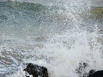 La doccia delle goccioline di acqua dovuto il mare ondeggia lo schianto sulle rocce immagine stock