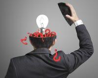 La domanda compilata dentro la testa dell'uomo d'affari con la lampada schiocca fuori sopra Fotografia Stock Libera da Diritti
