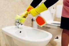 La domestica pulisce il bidet con uno spruzzo di pulizia fotografia stock libera da diritti