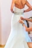 La domestique Buttoning de la jeune mariée la robe de mariage images stock