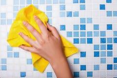 La domestique gaie nettoie la surface carrelée avec a photo stock