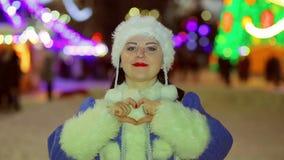 La doncella sonriente de la nieve muestra un corazón con sus manos almacen de video