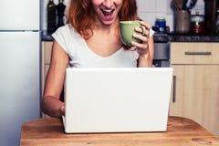 La donna è eccitata circa il suo computer portatile Immagini Stock