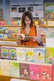 La donna è libro di lettura nella libreria aperta di buddismo. Fotografie Stock