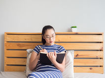 La donna è libro di lettura sul letto fotografia stock libera da diritti