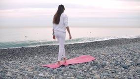 La donna è stuoia allegra di menzogne di yoga su Pebble Beach alla pratica di giorno stock footage