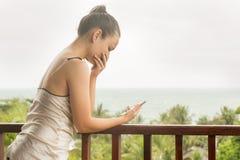 La donna è turbata dopo avere scoperto le cattive notizie sul telefono immagini stock