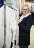 La donna è vestiti di compera nel deposito del tessuto sulla vendita Immagini Stock