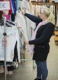 La donna è vestiti di compera nel deposito del tessuto sulla vendita Fotografia Stock