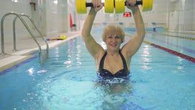 La donna abbastanza anziana fa l'esercizio con le teste di legno nella piscina stock footage