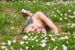 La donna abbastanza bionda dei giovani su un prato fiorisce Fotografia Stock Libera da Diritti