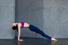 La donna abbastanza sottile nel reggiseno di sport e le ghette che fanno la plancia ascendente del rivestimento di yoga posano, p fotografie stock