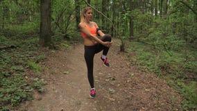 La donna abbastanza sportiva prima di correre nel parco impasta ed allunga i muscoli archivi video