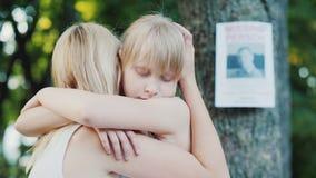 La donna abbraccia il bambino contro lo sfondo degli annunci mancanti di un uomo video d archivio