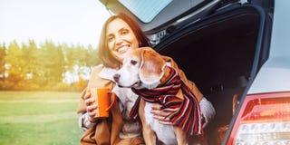 La donna abbraccia il suo cane del cane da lepre con gli scialli che si siedono insieme in automobile TR fotografia stock