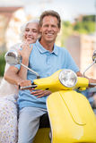 La donna abbraccia l'uomo sul motorino Fotografia Stock Libera da Diritti