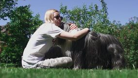 La donna accarezza il suo cane che si siede sull'erba archivi video