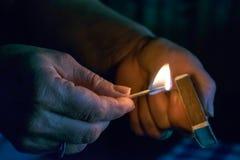 La donna accende una partita, fuoco da una partita Fotografia Stock Libera da Diritti