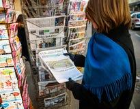 La donna acquista il giornale di periodi da un chiosco con Donald fotografia stock libera da diritti
