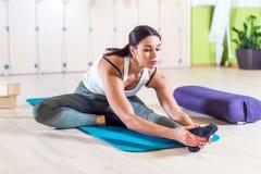 La donna adatta che fa allungando i pilates si esercita nello studio di forma fisica Fotografia Stock
