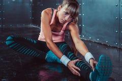 La donna adatta che fa l'allungamento esercita i suoi muscoli Fotografia Stock