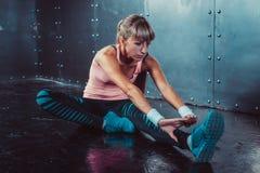 La donna adatta che fa l'allungamento esercita i suoi muscoli Immagini Stock Libere da Diritti