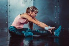 La donna adatta che fa l'allungamento esercita i suoi muscoli indietro e le gambe prima di un addestramento si scaldano a forma f Immagine Stock Libera da Diritti