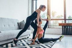 La donna adatta che fa l'allungamento si esercita con l'aiuto dell'amico che tiene la sua gamba a casa Fotografia Stock Libera da Diritti