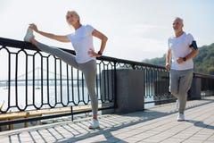 La donna adatta che fa l'allungamento si esercita mentre pareggiare dell'uomo Immagini Stock