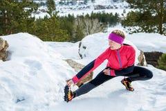 La donna adatta che fa l'allungamento si esercita prima di correre all'aperto Addestramento della via di inverno Immagine Stock Libera da Diritti