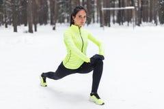 La donna adatta che fa l'allungamento si esercita prima di eseguire l'addestramento all'aperto di sguardo della via dell'inverno  Immagine Stock Libera da Diritti