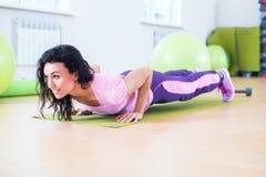 La donna adatta che fa l'esercizio della plancia e spinge aumenta lavorare al tricipite dei muscoli addominali fotografia stock