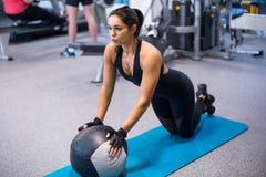 La donna adatta che si esercita con fare fuori di armi di allenamento della palla medica di esercizio di addestramento del tricip Fotografia Stock Libera da Diritti