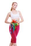 La donna adatta con la misura lega la frutta con un nastro. dimagramento di dieta. Fotografia Stock Libera da Diritti