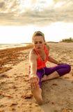La donna adatta dell'attivo negli sport innesta sull'allungamento del litorale Fotografia Stock Libera da Diritti