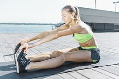La donna adatta di forma fisica che fa l'allungamento si esercita all'aperto al parco Immagine Stock