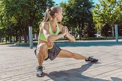 La donna adatta di forma fisica che fa l'allungamento si esercita all'aperto al parco Immagine Stock Libera da Diritti