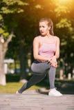 La donna adatta di forma fisica che fa l'allungamento si esercita all'aperto al parco Fotografia Stock